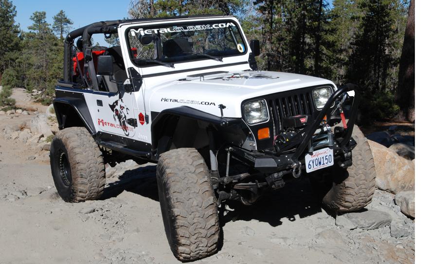 white Jeep YJ Wrangler driving over rocks